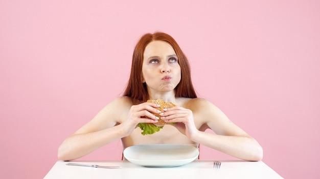 Chuda anoreksyjna dziewczyna łapczywie zjada hamburgera. zaburzenia odżywiania. anoreksja