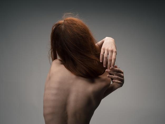 Chuda rudowłosa kobieta dotyka się rękami za plecami.