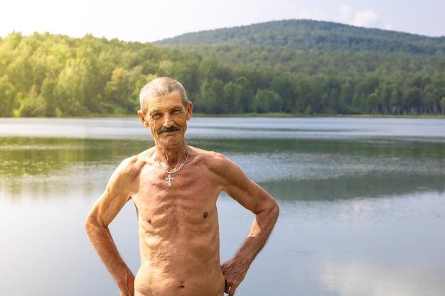 Chudy Starszy Mężczyzna Z Nagim Torsem Na Tle Krajobrazu Jeziora I Lasu Premium Zdjęcia