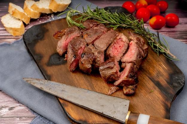Churrasco z mięsa pokrojonego na kawałki na drewnianej desce w rustykalnej oprawie. widok z lotu ptaka