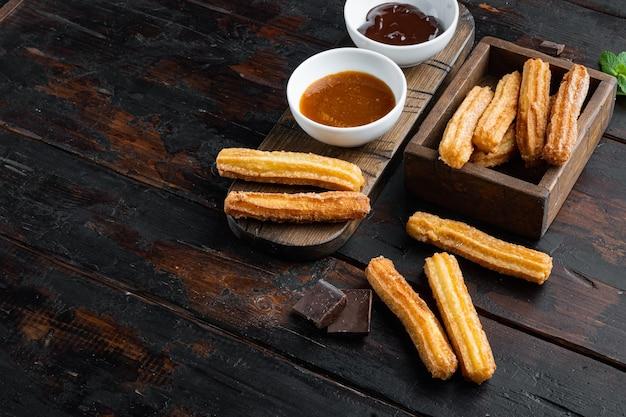 Churros z cukrem i sosem czekoladowym, na tle stary ciemny drewniany stół z miejscem na tekst, lato