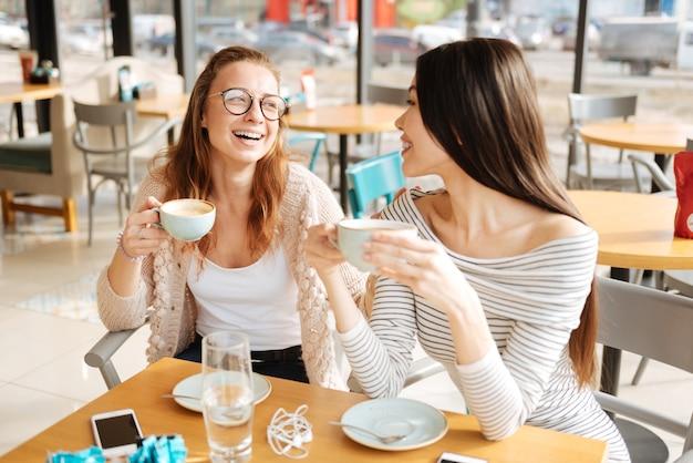 Chwila intencji. dwie najlepsze dziewczyny patrzą na siebie i uśmiechają się podczas spotkania w kawiarni.