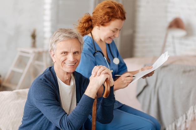 Chwila na analizę. przystojny, charyzmatyczny starszy pan przechodzący regularne badania i czekający na wyniki swoich badań, podczas gdy lekarz analizuje uzyskane dane
