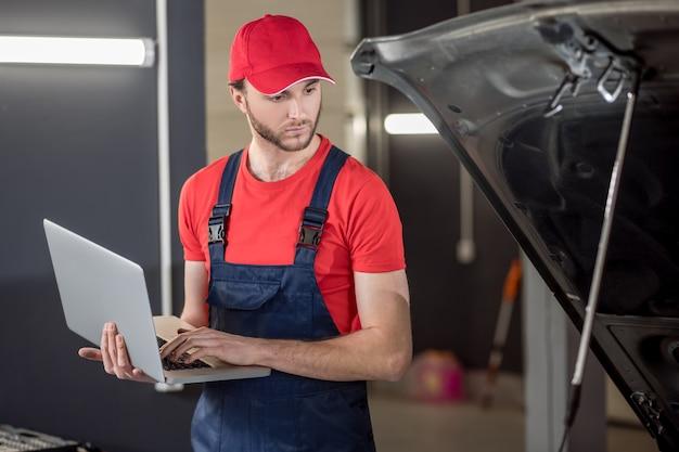 Chwila pracy. młody brodaty poważny zmartwiony mechanik samochodowy z laptopem patrząc pod maską samochodu w warsztacie