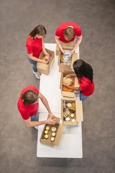 Chwila pracy. widok z góry młodych zaangażowanych wolontariuszy w czerwonych koszulkach, pakujących charytatywne kartony z artykułami spożywczymi i ubraniami