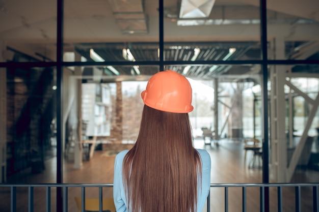 Chwila, refleksja. widok z tyłu długowłosej kobiety w kasku ochronnym i lekkiej bluzce stojącej spokojnie w myśleniu o nowym budynku