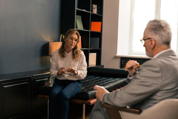Chwila smutku. przygnębiona kobieta siedząca na skraju kanapy, trzymająca w dłoni okulary i słuchająca psychologa