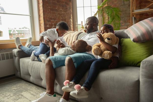 Chwile. młoda i wesoła afrykańska rodzina podczas kwarantanny, izolacji spędzających wspólnie czas w domu. czas na rodzinę, szczęście i miłość. koncepcja kwarantanny stylu życia, wspólnoty, domowego komfortu