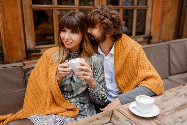 Chwile. relaksująca para zakochanych siedzi na tarasie i pije poranną kawę i delektuje się śniadaniem.