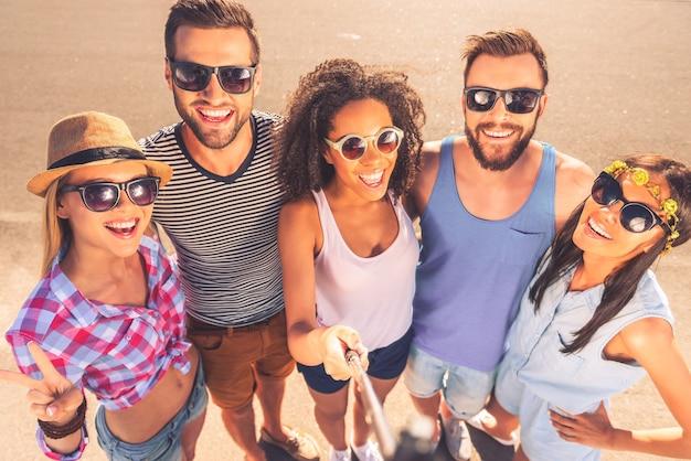 Chwile warte zapamiętania. widok z góry na grupę wesołych młodych ludzi robiących selfie, stojąc razem na zewnątrz