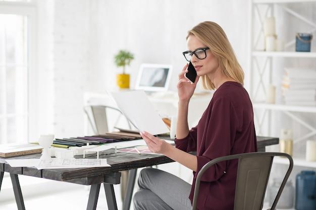 Chwileczkę. zamyślony skoncentrowany bizneswoman pozuje przy stole i nawiązywania połączeń