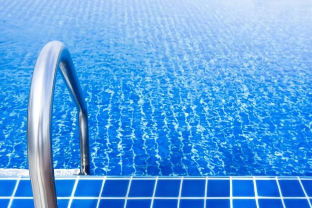 Chwyć pręty nierdzewne w niebieskim basenie