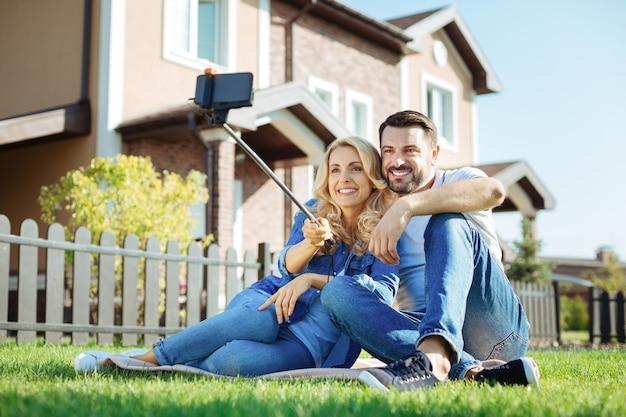 Chwytanie chwili. piękna młoda para siedzi na dywanie obok swojego niedawno kupionego domu i robi sobie razem selfie