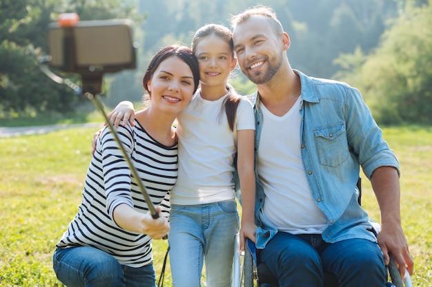 Chwytanie chwili. urocza młoda kobieta kucająca obok swojej córeczki i męża o ograniczonej sprawności ruchowej i robiąca grupowe selfie z kijem do selfie