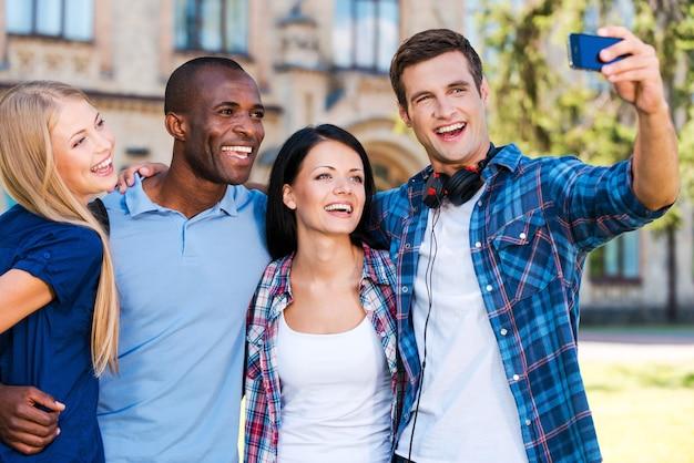 Chwytanie chwili z życia studenckiego. czterech szczęśliwych młodych ludzi robi selfie, stojąc blisko siebie na zewnątrz