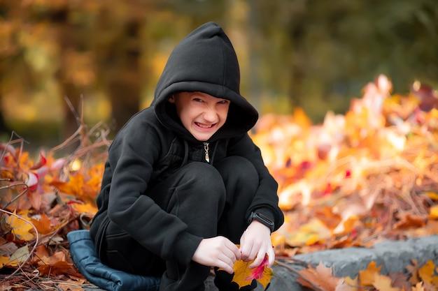 Chytry chłopiec w czarnej kurtce z kapturem siedzi na krawężniku i uśmiecha się