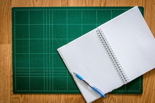 Ciąć maty, notatnik, pióro na drewnianym tle
