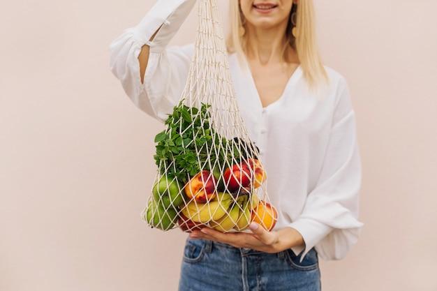 Ciąg torba na zakupy z owocami w rękach młodej kobiety. torba ekologiczna wielokrotnego użytku na zakupy
