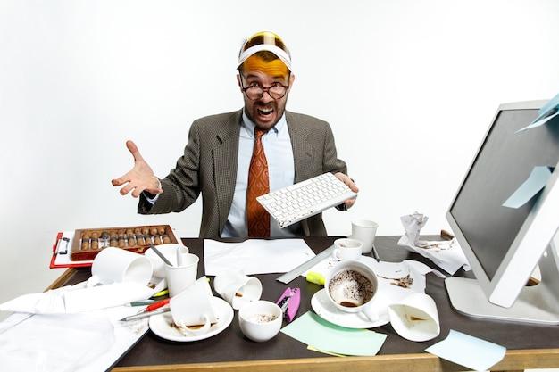 Ciągła awaria. młody człowiek rozlał napój na klawiaturze podczas pracy i próbując się obudzić. picie dużo kawy. pojęcie kłopotów, biznesu, problemów i stresu pracownika biurowego.