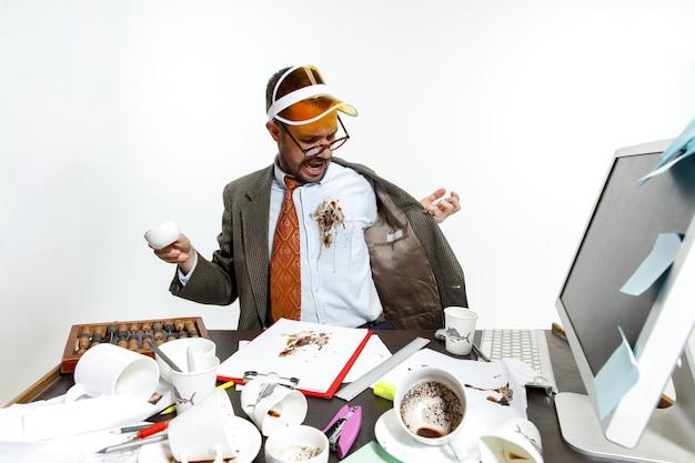Ciągła awaria. młody człowiek wylał napój na białą koszulę podczas pracy i próbując się obudzić. picie dużo kawy. pojęcie kłopotów, biznesu, problemów i stresu pracownika biurowego.