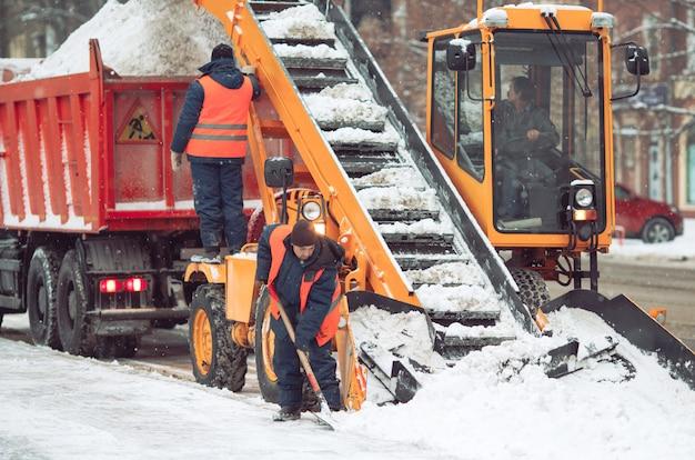 Ciągnik do sprzątania śniegu maszyna do usuwania śniegu ładowanie kupy śniegu na wywrotkę.