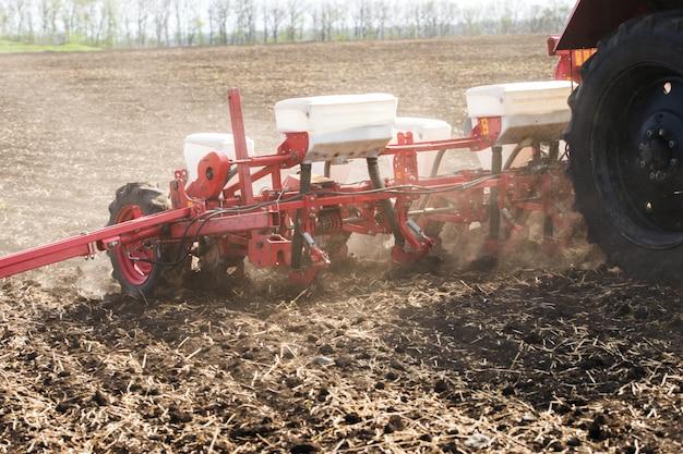 Ciągnik na polu czarnej ziemi z ciągnionymi siewnikami rolniczymi