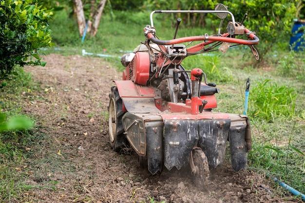 Ciągnik odgarniający glebę na plantacji rowków