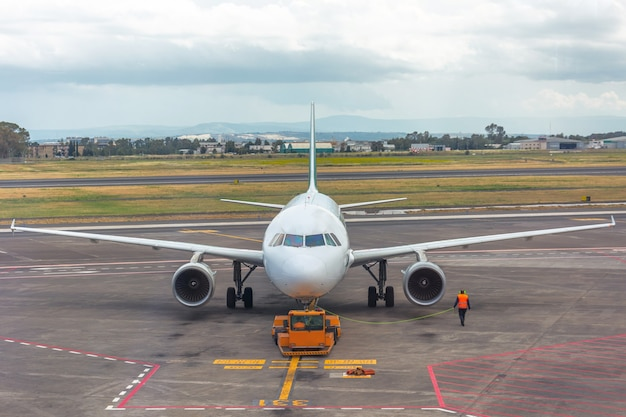 Ciągnik odpychający holuje samolot na parking, marszałek lotnictwa.