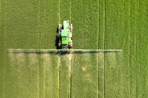 Ciągnik opryskiwania pestycydów chemicznych z opryskiwacza na dużym zielonym polu rolnym na wiosnę.