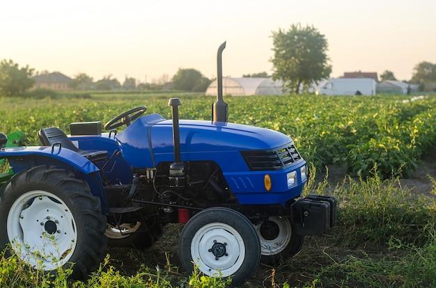 Ciągnik rolniczy bez kierowcy stoi na polu farmy o zachodzie słońca. dofinansowanie i wspieranie gospodarstw