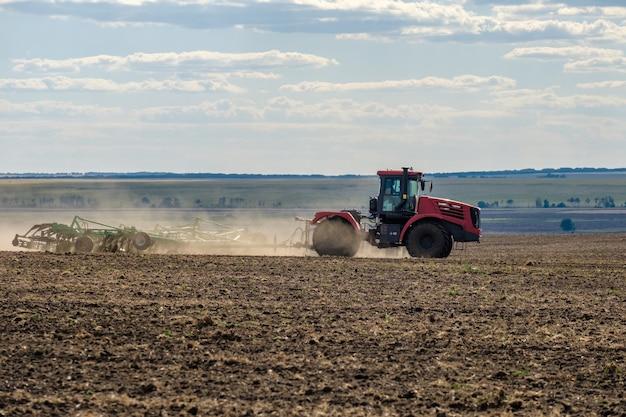 Ciągnik rolniczy w chmurze pyłu kultywuje glebę na polu za pomocą kultywatora po zbiorach