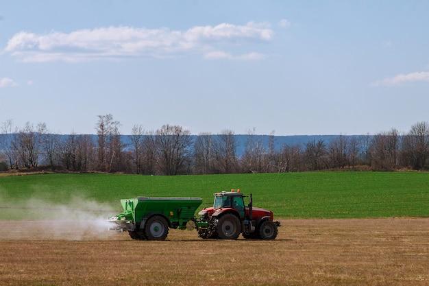 Ciągnik rozprowadzający nawóz na polu trawy. praca w rolnictwie.