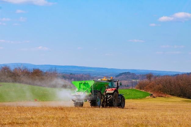 Ciągnik rozrzuca nawóz granulowany na polu trawiastym. prace rolnicze. azotan. nawozy mineralne.