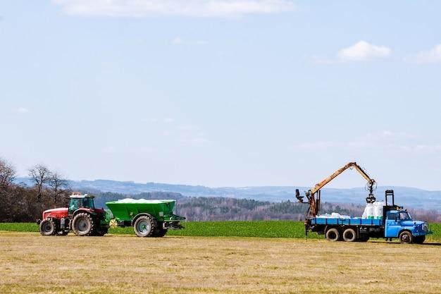 Ciągnik rozsiewający nawóz na polu trawy. prace rolnicze.