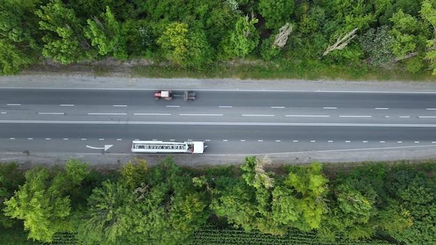 Ciągnik siodłowy i samochody, widok z góry na asfaltową drogę wysoko nad drzewami.