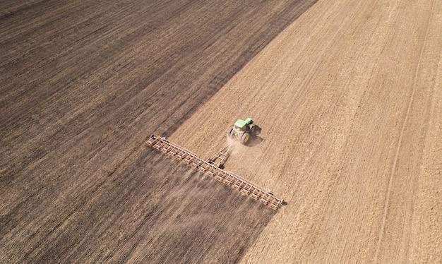 Ciągnik uprawia glebę. aby zatrzymać wilgoć wczesną wiosną. widok z lotu ptaka.