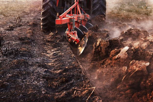 Ciągnik uprawia glebę, przygotowując ją pod uprawę rolniczą.