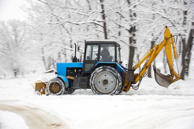 Ciągnik w ciemnoniebieskim kolorze usuwa śnieg w parku