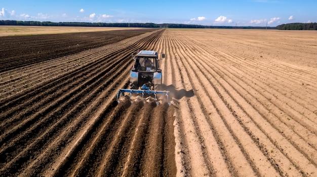 Ciągnik - widok z lotu ptaka ciągnika przy pracy - uprawa pola wiosną z niebieskim niebem - maszyny rolnicze