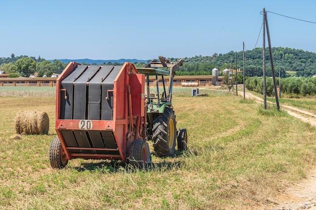 Ciągnik z prasą do słomy obok gospodarstwa.
