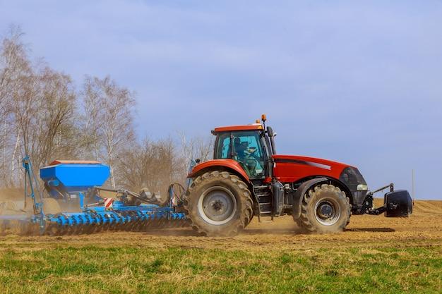 Ciągnik z siewnikiem zbóż na polu. pojęcie agronomii.