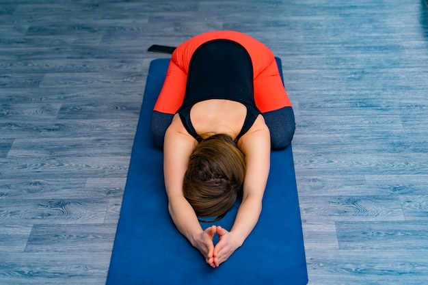 Ciało kobiety leżące na macie z opuszczoną głową i relaksujące podczas treningu. młoda sportowa kobieta w odzieży sportowej, ćwiczenia jogi i ćwiczenia oddechowe w studio jogi.