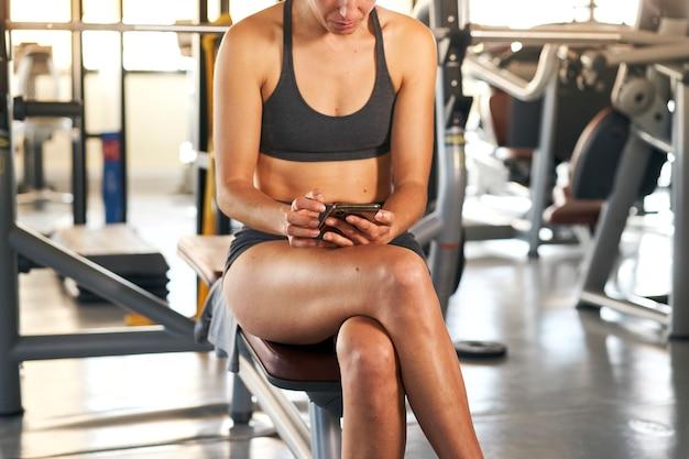Ciało kobiety sportowca za pomocą telefonu komórkowego w siłowni w odzieży sportowej sprawdzanie telefonu podczas odpoczynku po treningu na ławce, wysyłanie wiadomości ze smartfona.