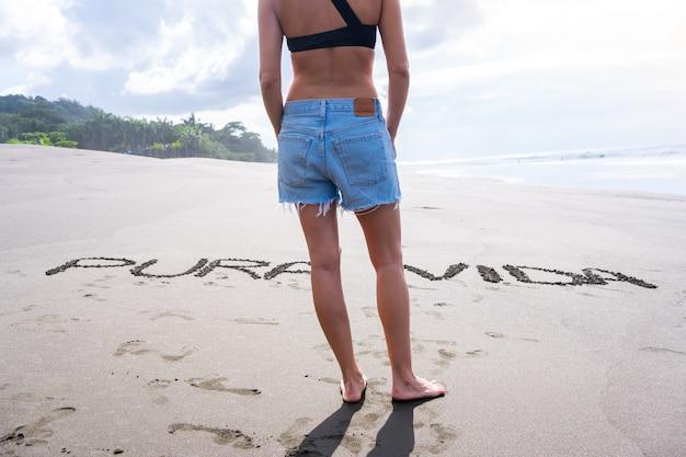 Ciało kobiety w letnim stroju stojącej przed literami wypisanymi na piasku plaży