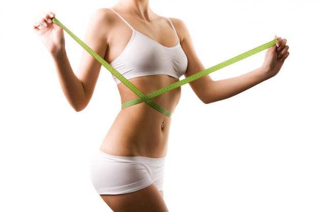 Ciało młodej kobiety w białych szortach i górnej talii pomiarowej z centymetrem w ręce nad białym