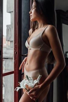 Ciało młodej kobiety z gładką skórą i kwiatem lilii