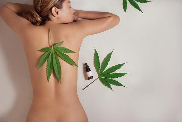 Ciało nagiej kobiety z płynnym olejem cbd z ekstraktu z konopi indyjskich do naturalnej pielęgnacji skóry. na białym tle na szarym tle