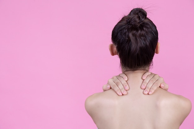 Ciało pięknej młodej dziewczyny na różowej ścianie, nagie zdjęcie.