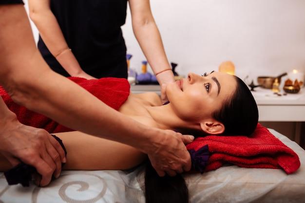Ciasne torby. ciemnowłosa piękna klientka zrelaksowana podczas delikatnego masażu w profesjonalnym salonie kosmetycznym