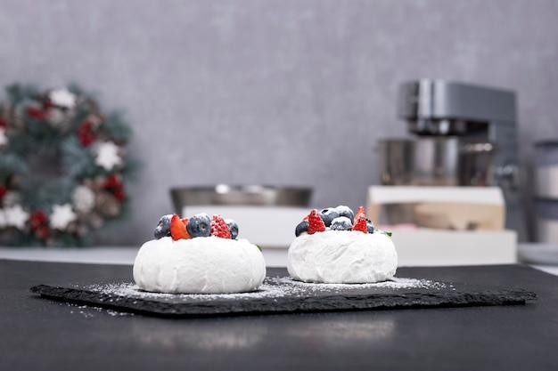Ciasta anna pawłowa. dmuchane ciasta marshmallow i świeże jagody.